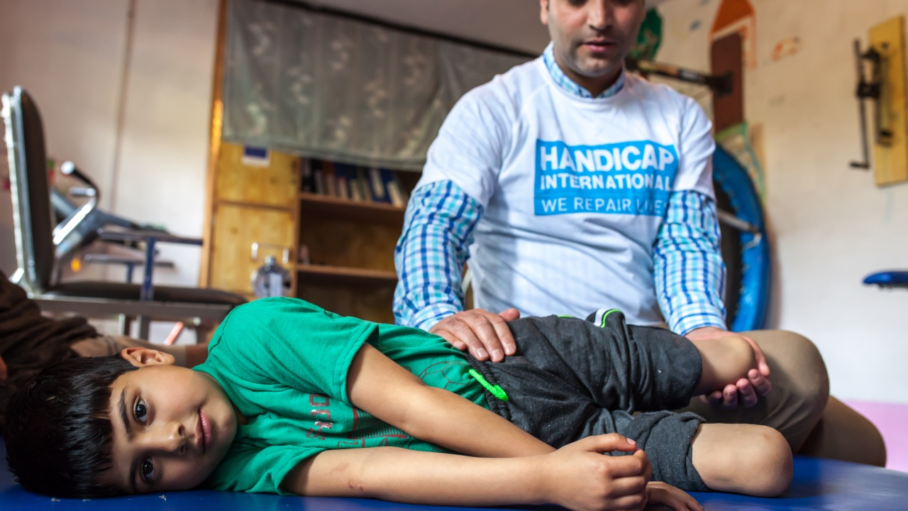 Fayaz during a rehabilitation session with Muddasir Ashraf, a physiotherapist and Disability Manager for Handicap International; }}