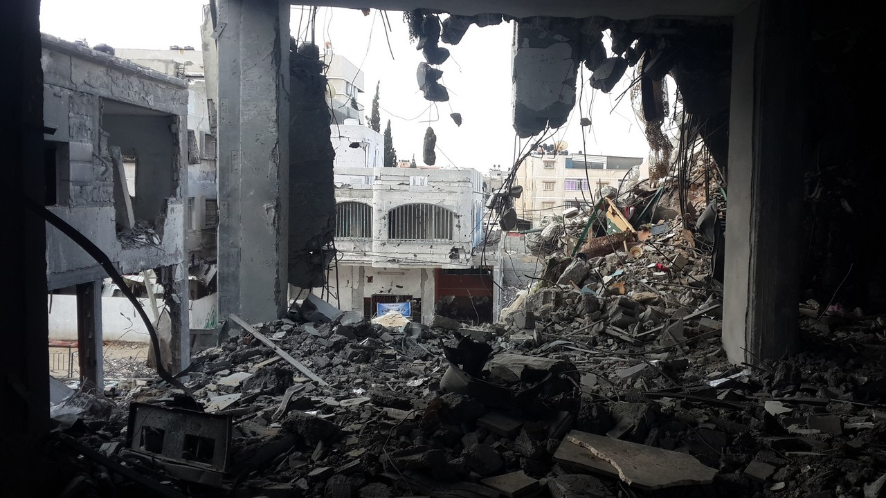 A photo of a building destroyed by air-strikes in teh summer of 2014. Gaza.; }}