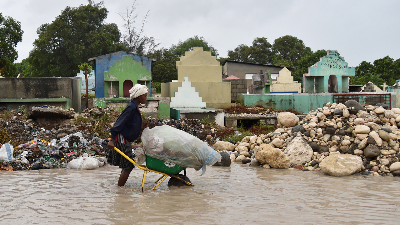 A woman pushes a wheelbarrow while walking in a partially flooded street, in the Haitian capital, Port-au-Prince, on October 4, 2016.