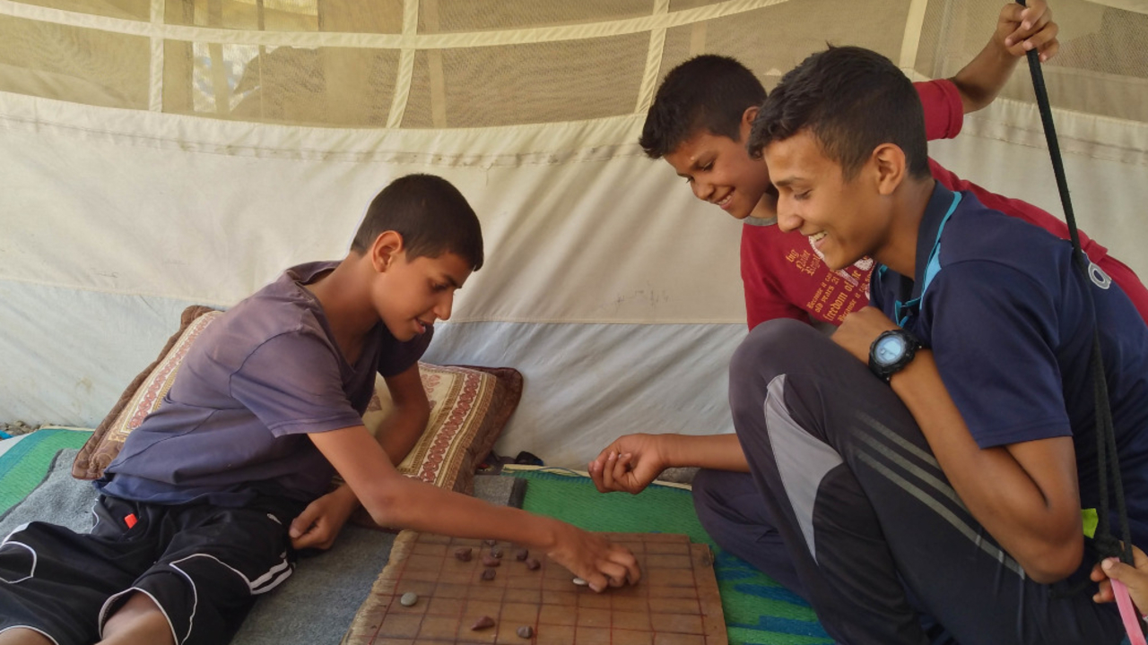 Abdallah and his older brother play draughts in their tent.; }}