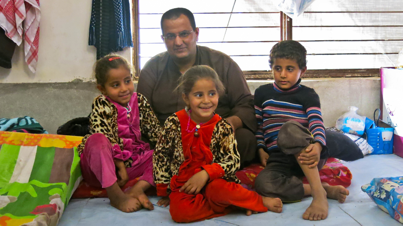 Gaylan and his children in their temporary shelter in Hasansham camp.; }}
