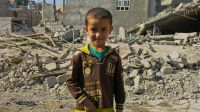 A child stands in front of damaged buildings in Jalawla, Iraq.; }}