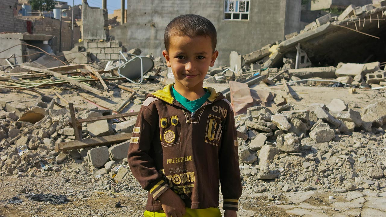 A child stands in front of damaged buildings in Jalawla, Iraq.