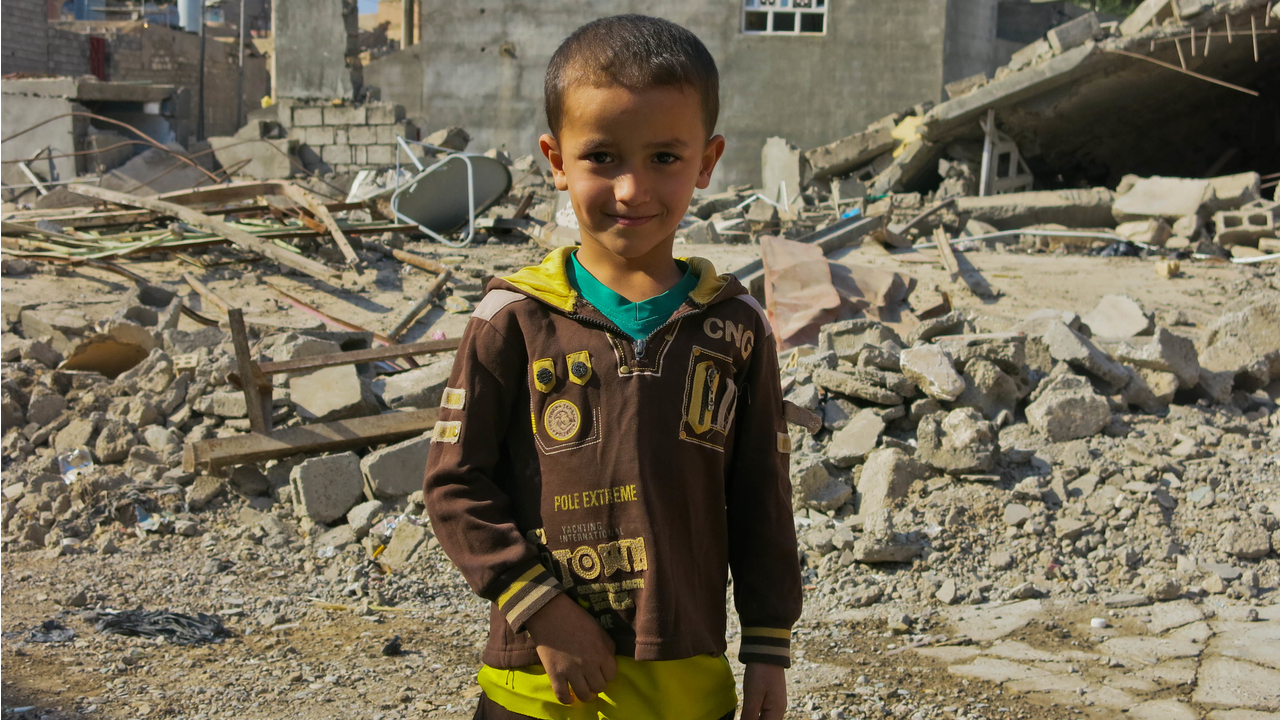 Khaled's son, in front of his uncle's ruined home.