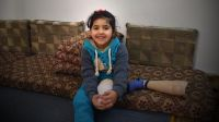 Salam sitting on the sofa with her prosthetic leg; }}