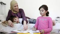 Haya, a disabled SYrian refugee, with her two children.