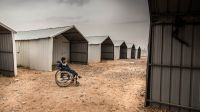 A disabled Syrian child sitting in a wheelchair in Azraq camp, Jordan.; }}