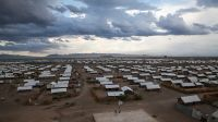 Landscape shot of Kakuma camp with clouds overhead; }}