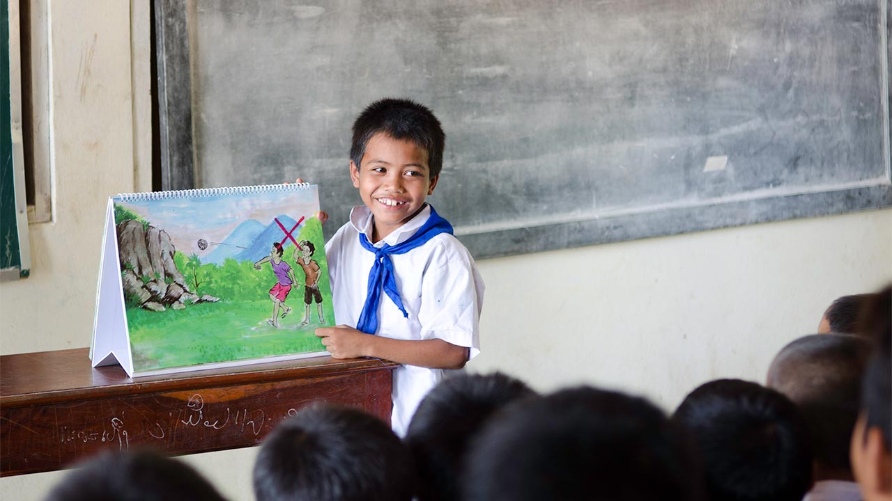 A young boy explains the risks from UXO to his classmates during a risk education session in Pounseeyerng village, Laos.; }}