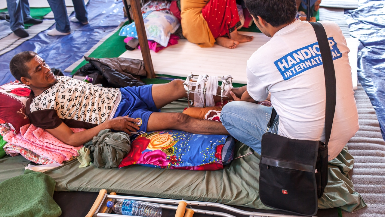A Handicap International physiotherapist assesses an earthquake survivor with a fracture. Nepal