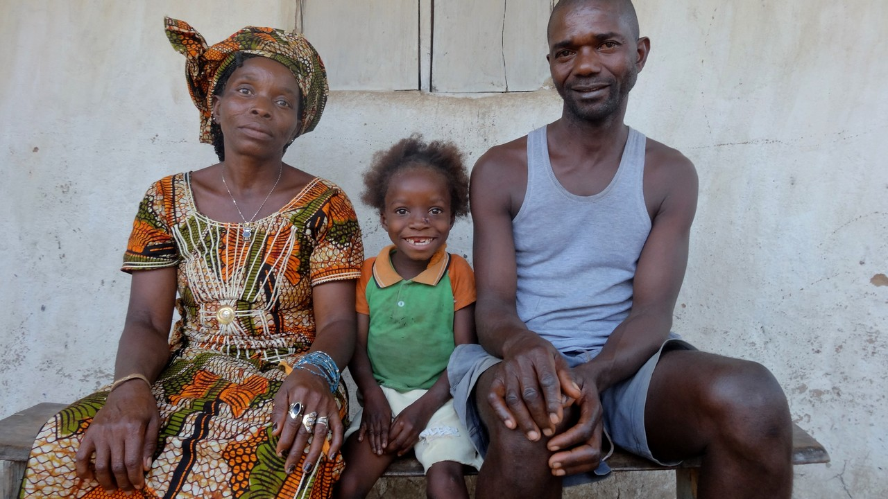 Eight-year-old Fanta, who has cerebral palsy, with her parents. Sierra Leone.
