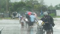 People wade through floods waters on the road from Veechikalmunai to Batticaloa. Sri Lanka.