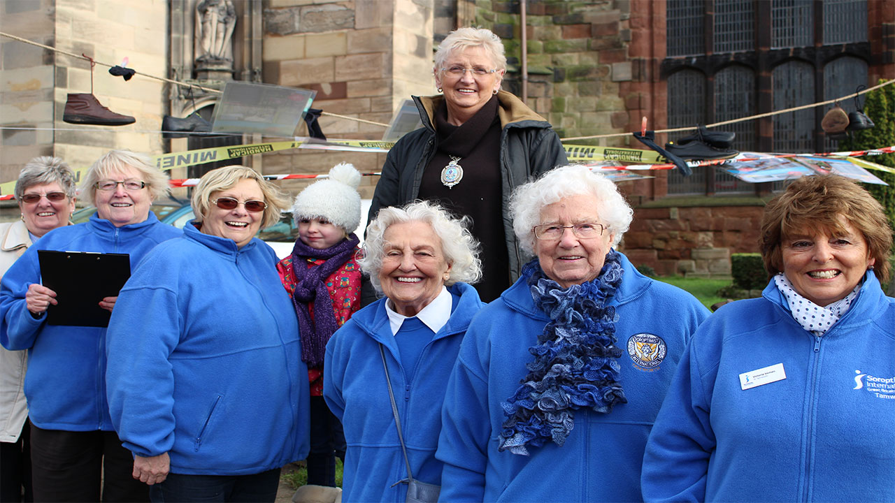 Tamworth Soroptimists outside St. Editha's Church where they built a Pyramid of Shoes on a windy Friday morning.