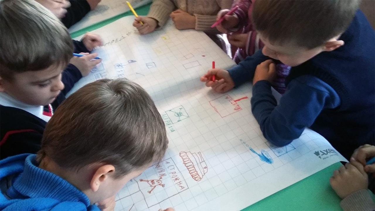 Children drawing situations where they might encounter mines, during a risk education session in Ukraine ; }}