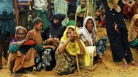 Women in a refugee camp waiting for food aid; }}