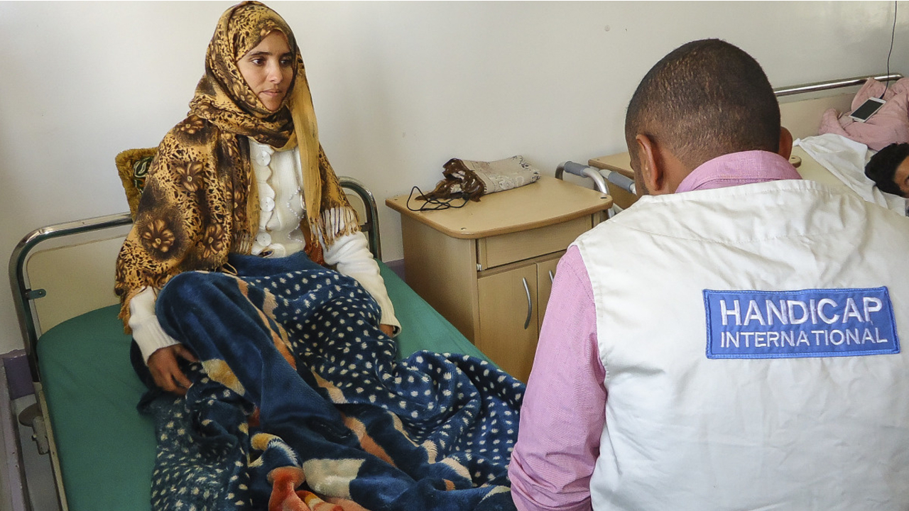 Saeed, a Handicap International physiotherapist, with a patient at the Al-Thawra hospital in Sanaa, one of the main hospitals providing care for victims of the conflict.