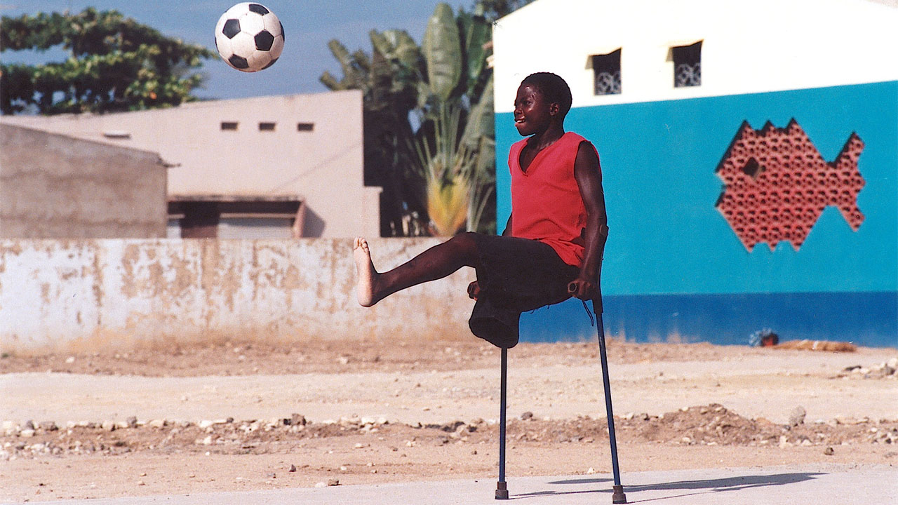 An amputee kicking a football, Angola